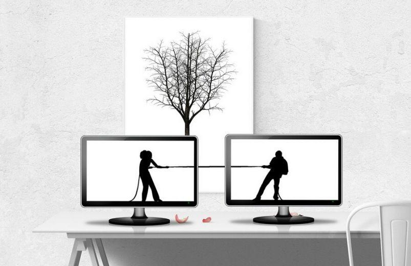 Mann und Frau in Monitoren ziehen an zwei Enden eines Seils