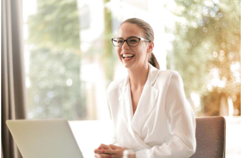 Mitarbeiterin vor dem Laptop lächelnd am Arbeitsplatz