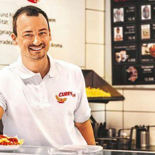 interne Seminare FeedbackMirko Großmann bei Curry 36 mit Currywurst und Pommes am Fenster